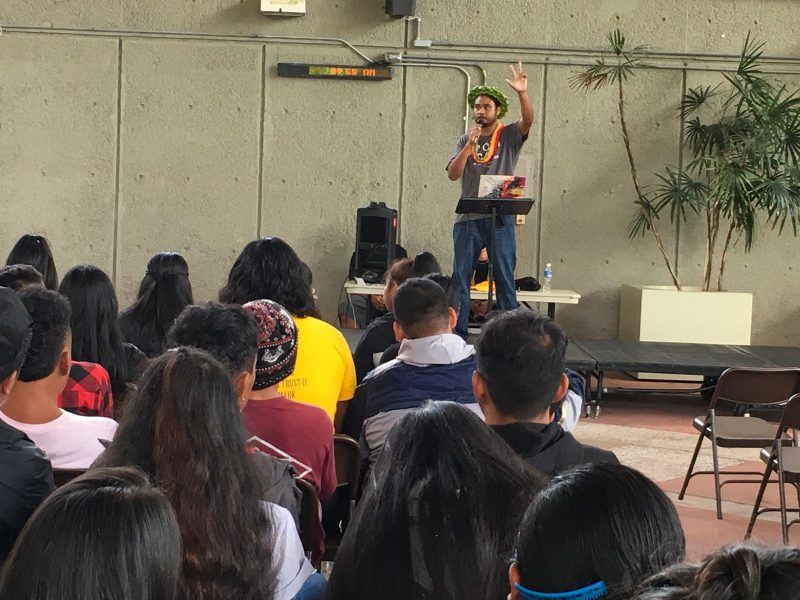 Dwayne Anefal on stage, with arm raised as he speaks to students.