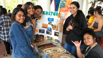 Group of students at an information table with poster board on KOSRAE, some photos are on the board.