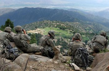 Army soldiers sitting on a rocky hill
