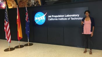 Andrea stands next to large signage: NASA Jet Propulsion Laboratory, California Institute of Technology. At left are US flag and other flags.