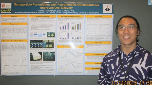 Younf man stands next tp his poster presentation on nanoparticles.