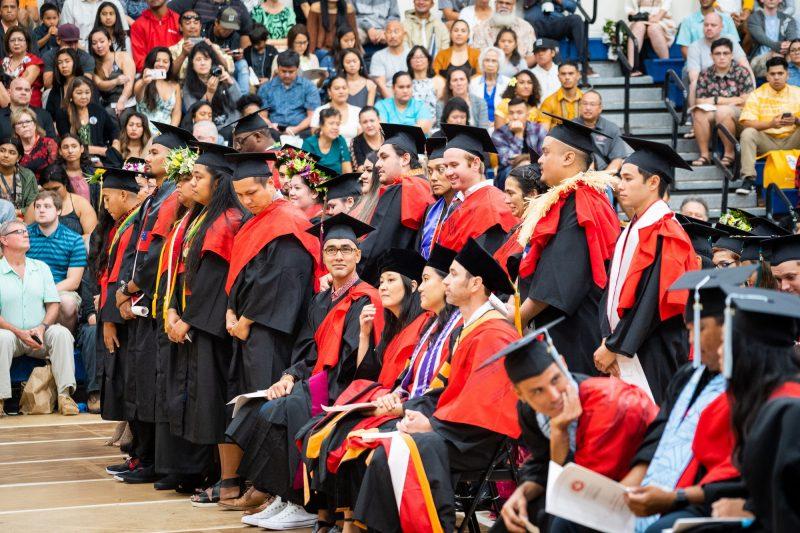 Graduates stand to walk toward dais.