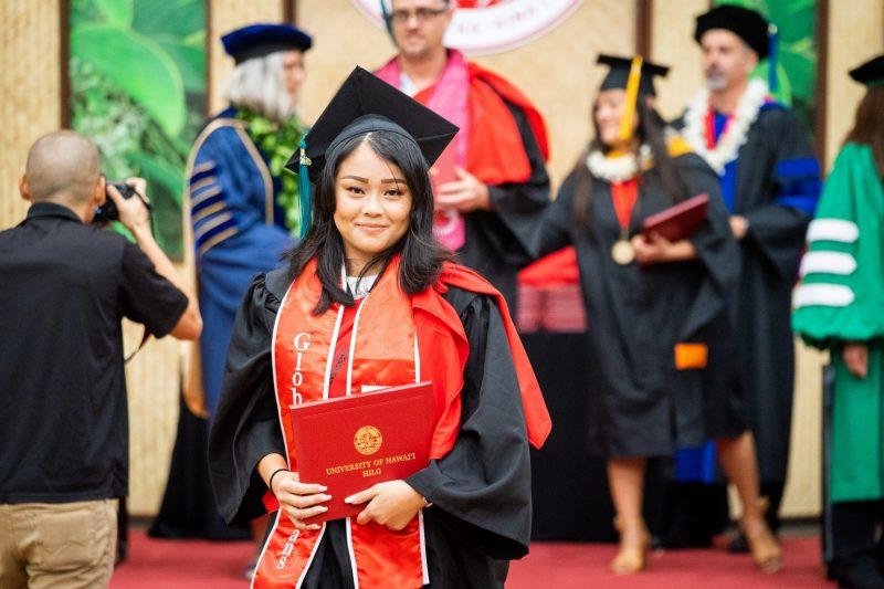 Woman graduate with shoulder length black hair descends dais holding diploma.