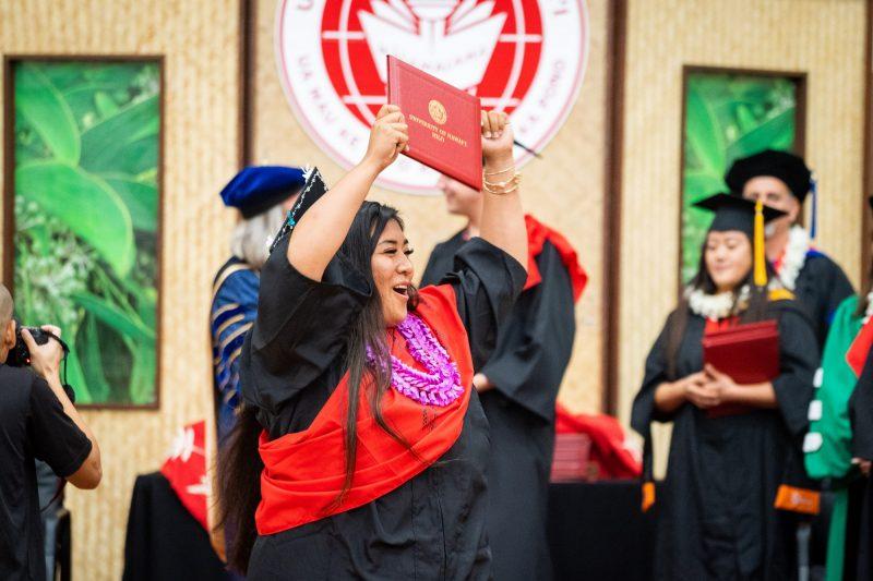 Woman graduate in purple lei holds diploma overhead.