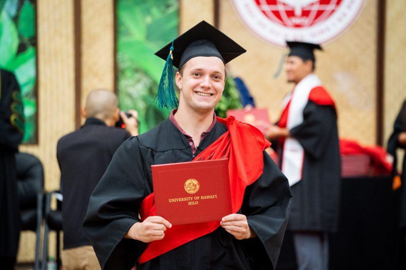 Man graduate holds diploma.