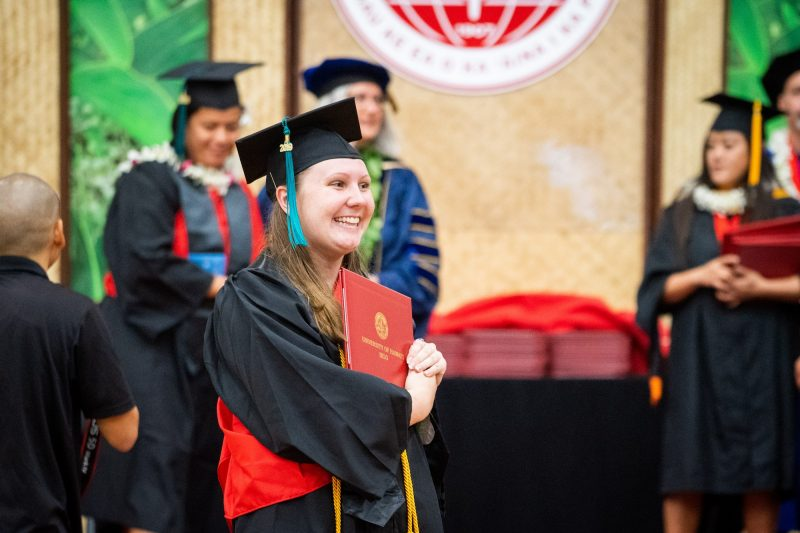Side view of woman graduate holding diploma.