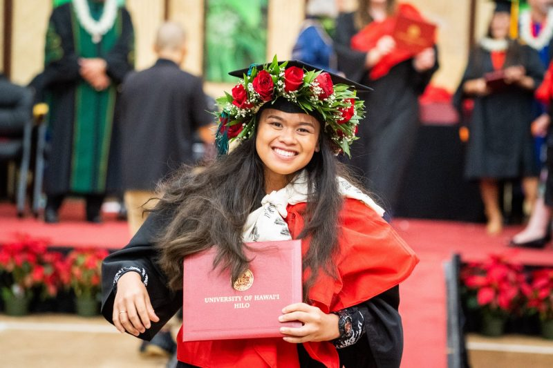 Woman graduate with red haku lei holds diploma.