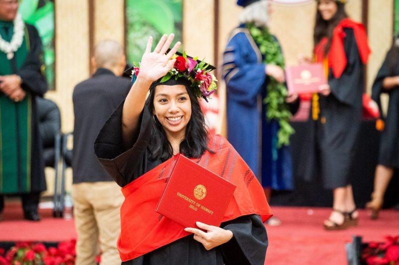 Female graduate in red halu lei waves to audience.