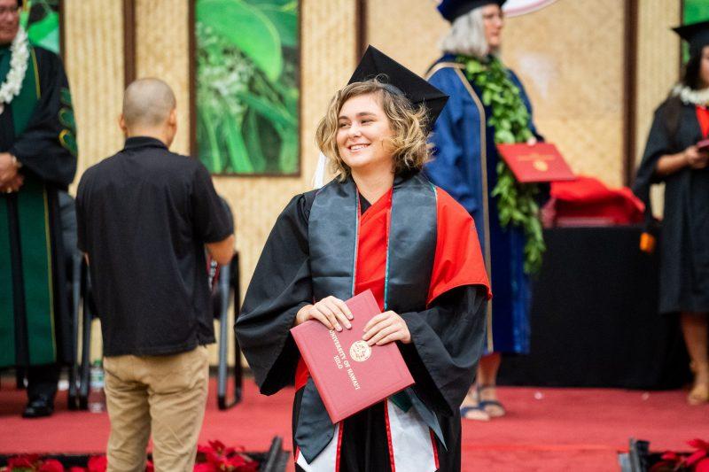 Graduate with black sash holds diploma.