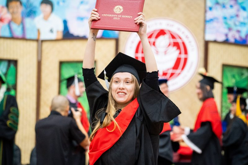 Graduate with red sash holds diploma high overhead.