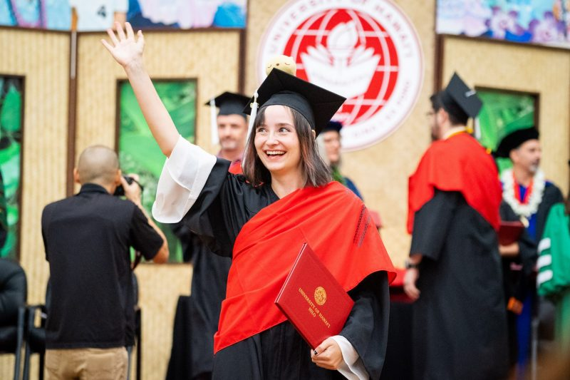 Woman graduate with red sash and white sleeves, waves to audience.