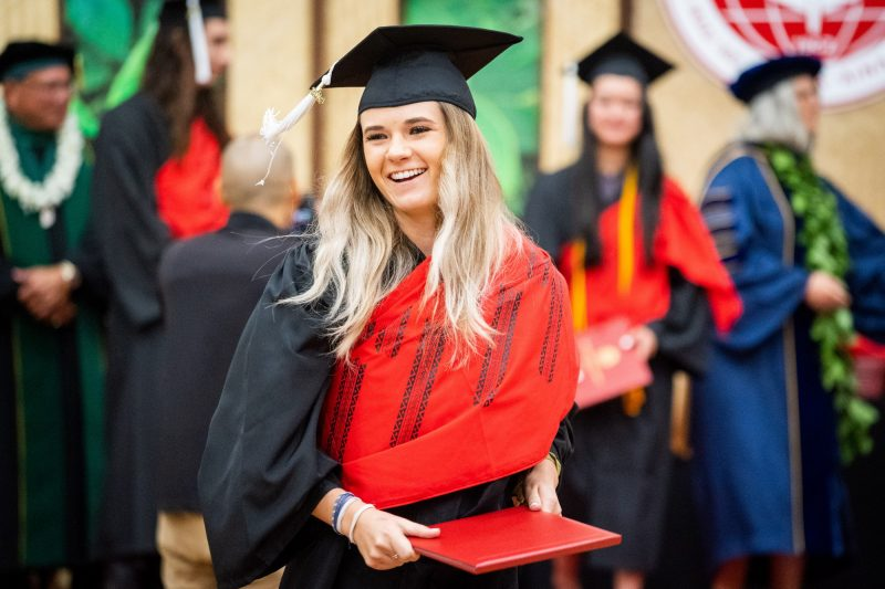Female graduate looks to her right.