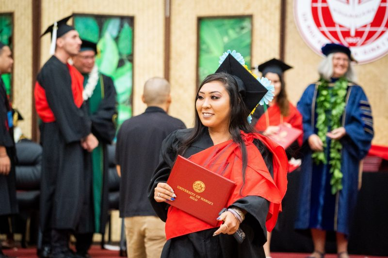 Female graduate with black hair looks to her right.