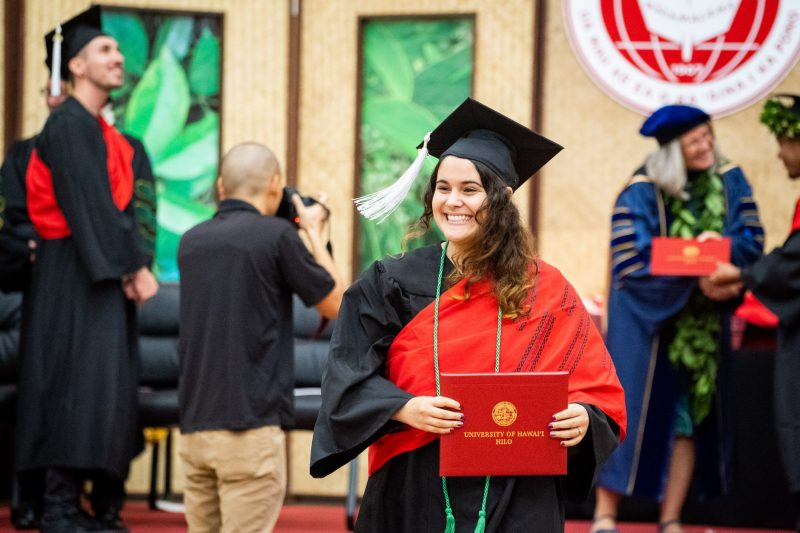 Female graduate with green cord smiles.