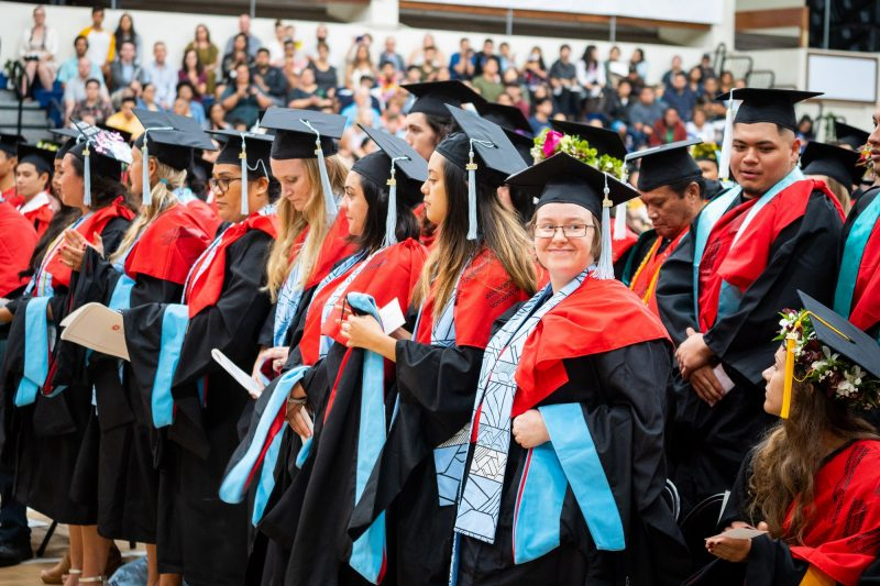 Graduates with blue sashes rise to receive degrees.