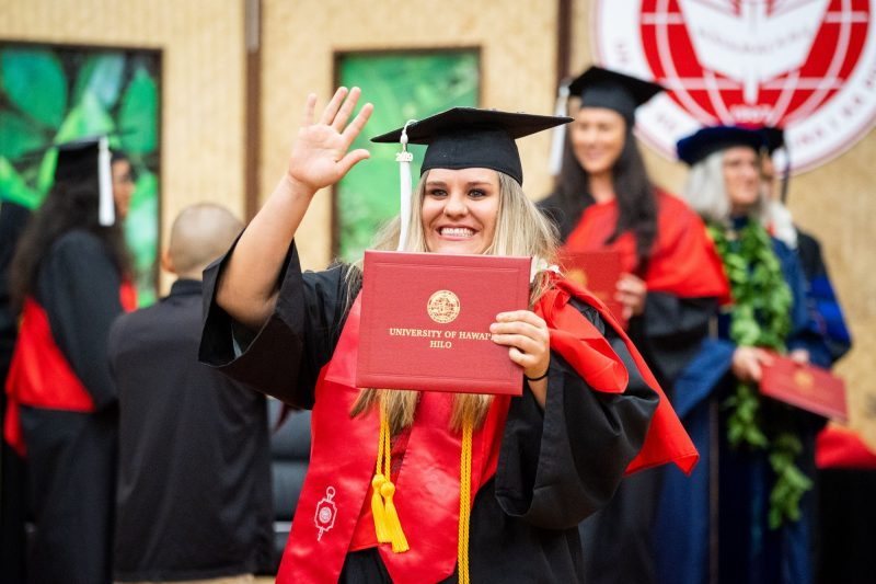 Female graduate holds diploma close to her face and waves to audience.