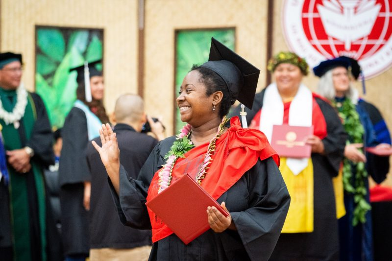 Woman graduate with lei big smile turns to her right and waves.