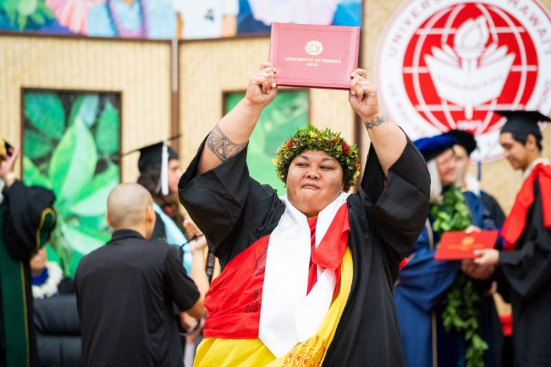Female graduate with haku and white sahs holds diploma over her head.