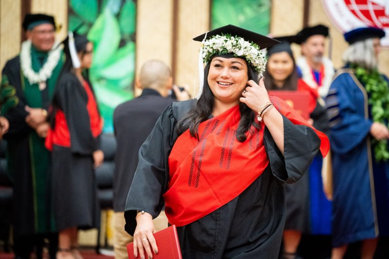 Female graduate brushes her hair away as she descends the dais.