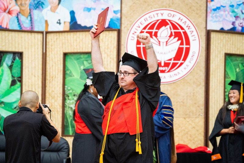 Male graduate holds both arms high, holding diploma.