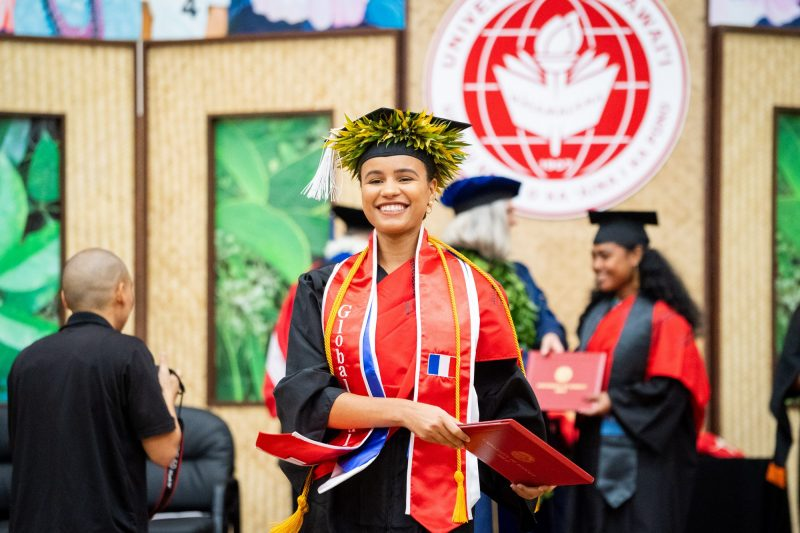 Woman graduate in wide red sash.