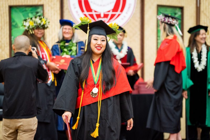 Woman graduate with long black hair and gold cord descends dais after receiving degree