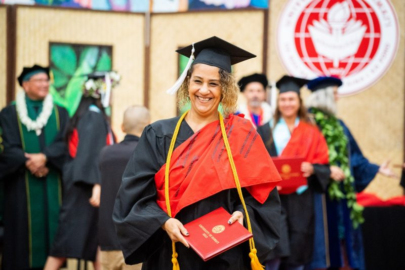 Woman graduate with curly hair big smile.
