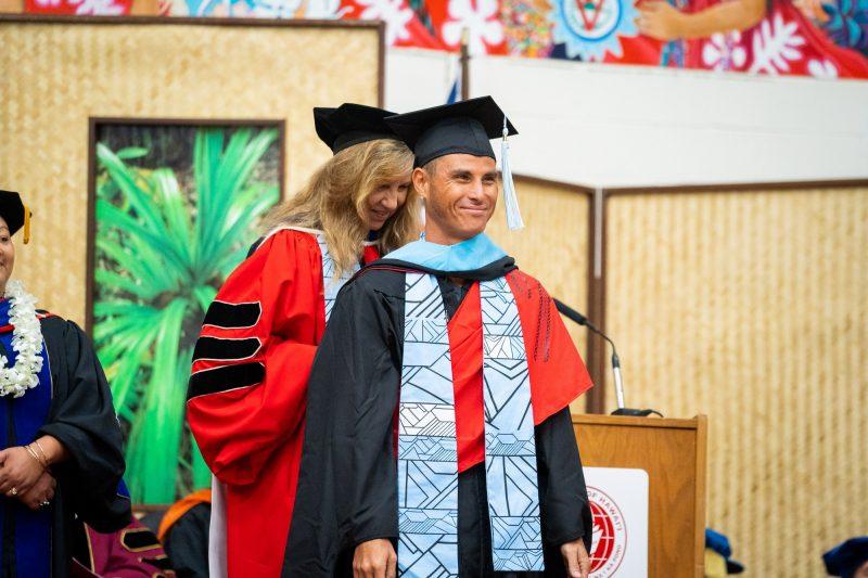A male graduate receives his blue hood.