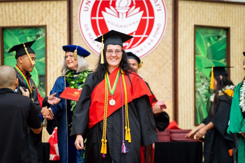 Woman graduate with gold cord and medals descends dais after receiving degree