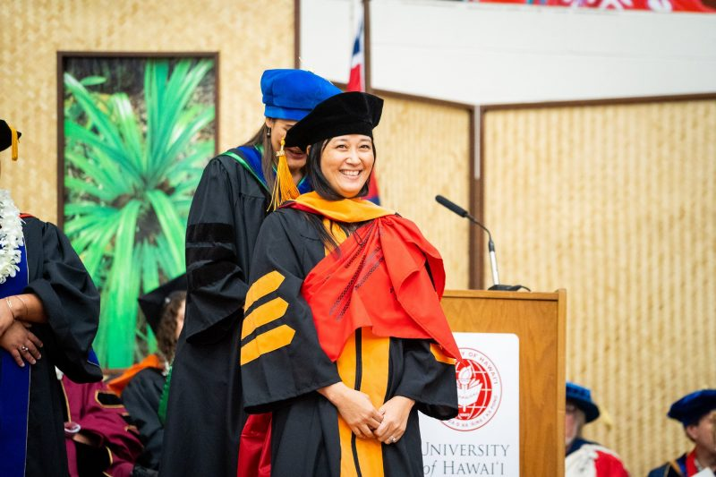 Female graduate with red sash stands while gold hood is placed on her shoulders
