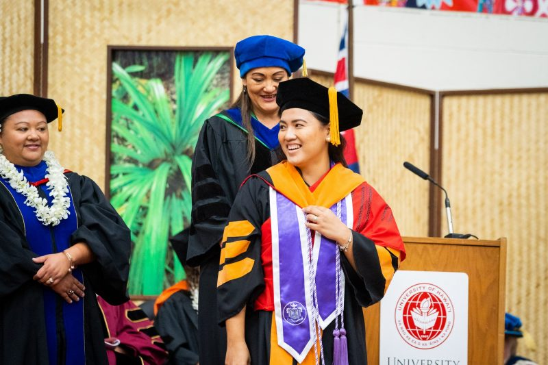 Female graduate with purple sash receives gold hood.