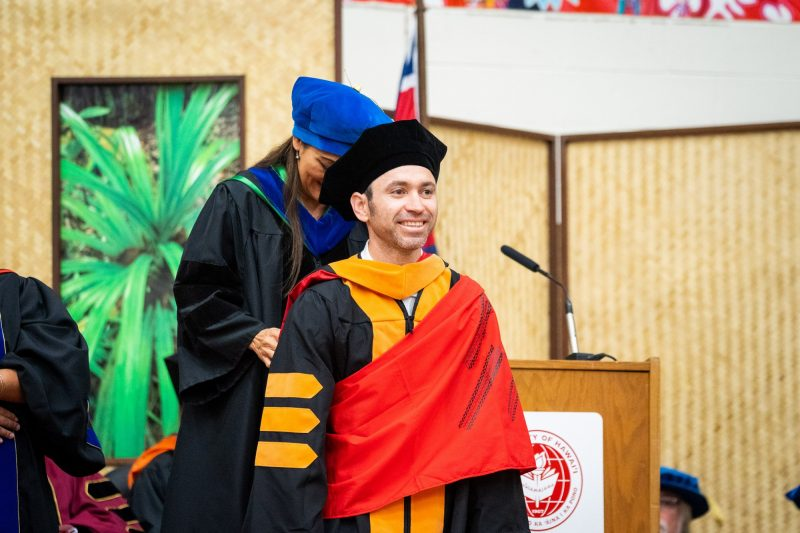 Male graduate with red sash receives gold hood.