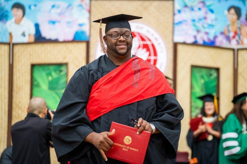 Male graduate with diploma and flashing shaka.