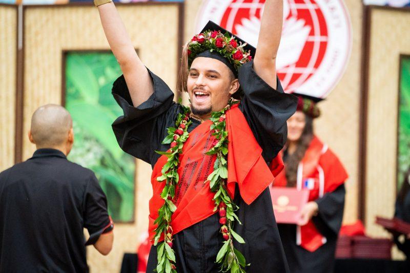 Male graduate raises diploma high overhead.
