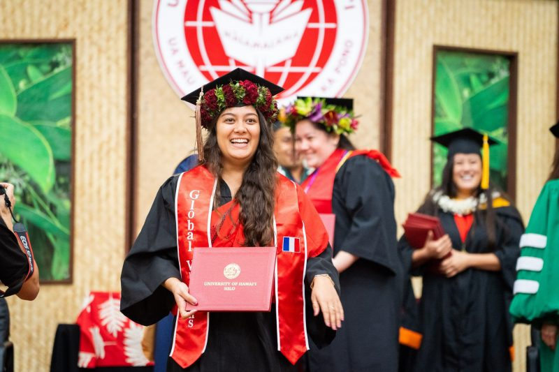 Female graduate with red sash descends dais with diploma.
