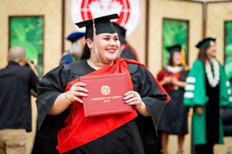 Woman graduate holds diploma to her chest as she descends dais.