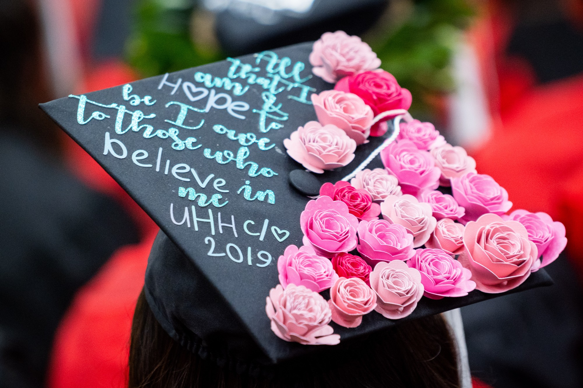 A close up of a mortarboard with flowers and the words: All that I am & hope to be I owe to those who believe in me, UHH 2019.