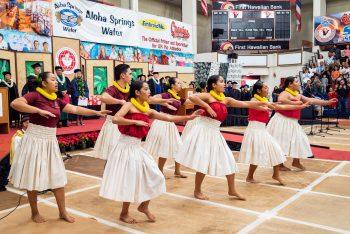 Hula dancers in white skirts.