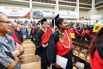 Processional, woman graduate in lei.