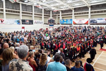 A wide view of graduates standing at their seats.