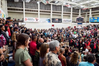 Wide view showing graduates and people in the stands.