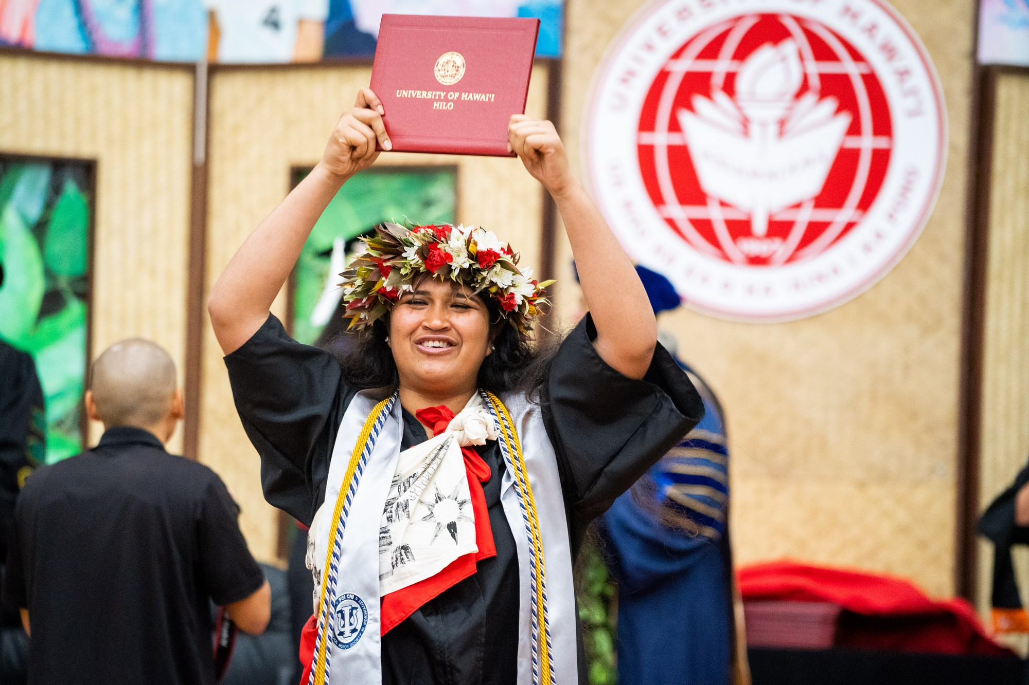 Woman graduate descends from the dais holding diploma overhead