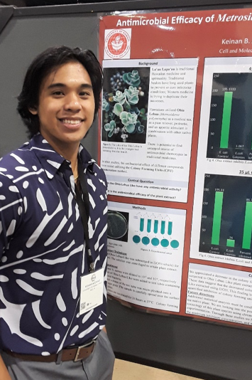 Keinan Agonias stands next to his poster presentation on antimicrobial effecacy.
