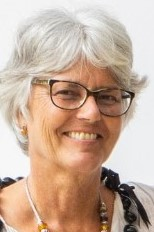Kirsten Møllegaard wearing glasses and smiling at the camera
