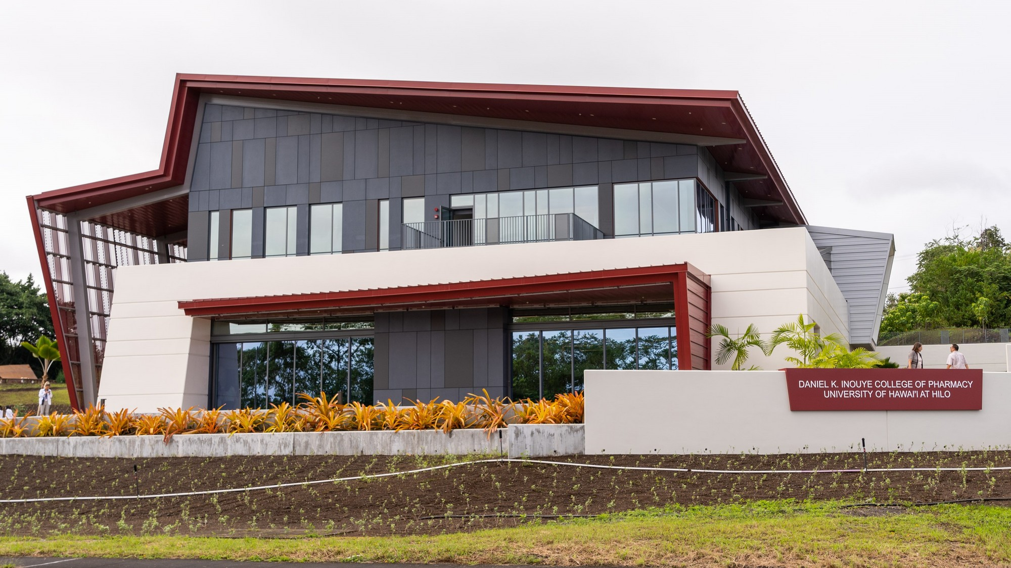 Two-story building, contemporary design, angled red rooftop, lots of windows, newly planted gardens in front. Signage: Daniel. K. Inouye College of Pharmacy, University of Hawaii at Hilo.