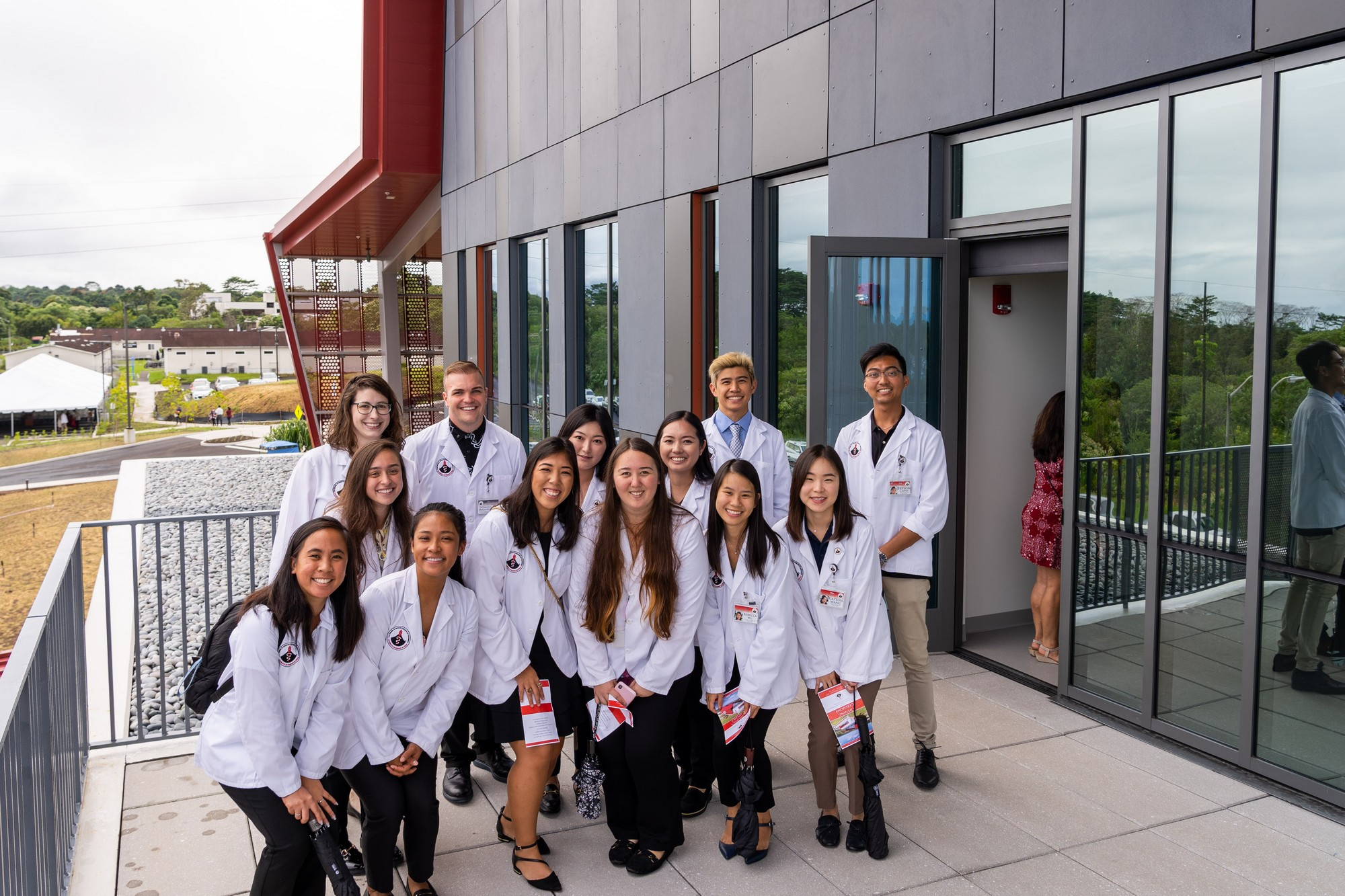 Group of pharmacy students in their white coats pose for photo on lanai of new building.