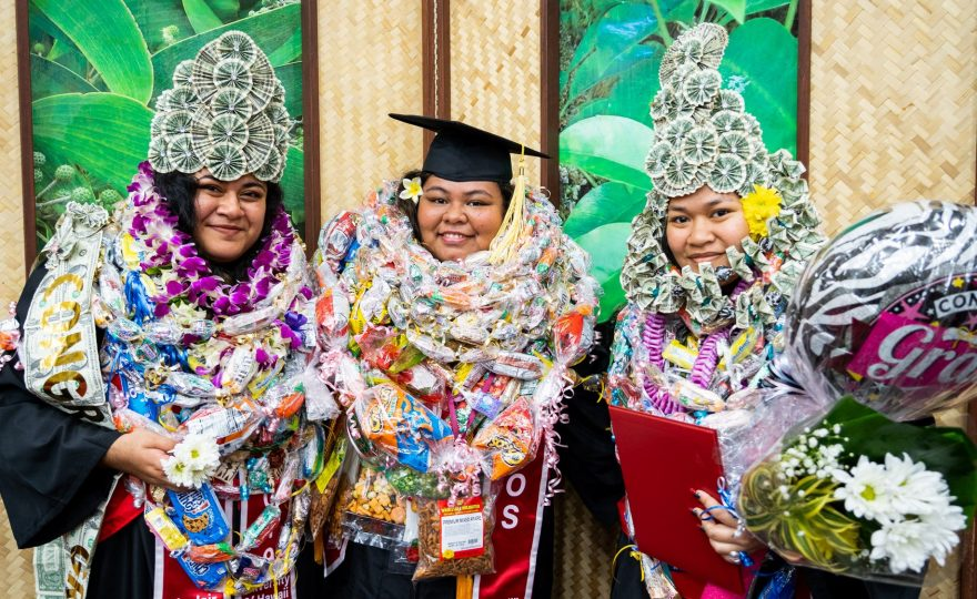 Three graduates, two with head dresses