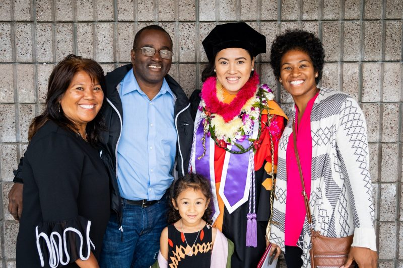 Family with young girl poses for photo with graduate.