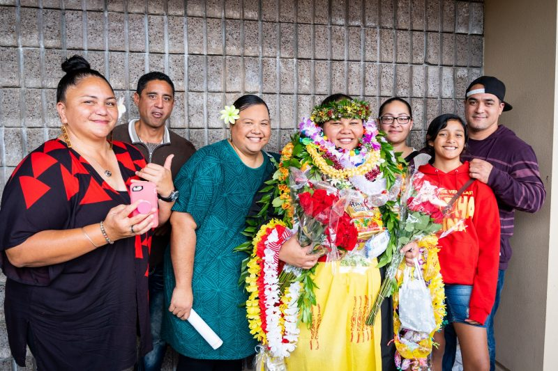 Family poses with graduate bedecked in lei.