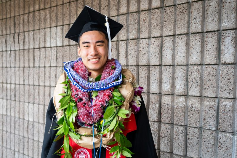 Man graduate with many lei.